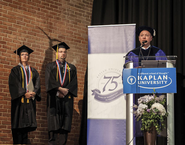 W. Christopher Motz, president of the Maryland campuses of Kaplan University, speaks Sunday during the fall commencement ceremony for the Hagerstown campus at North Hagerstown High School. Also pictured are student speakers Debra Stottlemyer, left, and Aaron Richards.