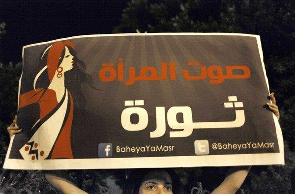 """An activist carries a sign that reads, """"The woman's voice is a revolution,"""" during a demonstration this month in Cairo protesting Egypt's constitutional assembly."""