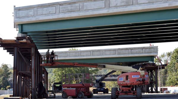 Left to right, Oscar Codoba and Walter Martines, of P&S Painting, do touch-up work on the underside of the new northbound West Nursery Road span, which will replace the existing bridge over the Baltimore-Washington Parkway.