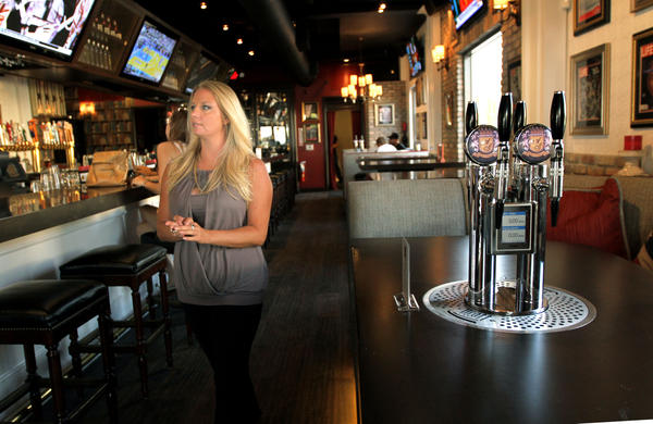 Hostess Katie Movat walks past a tap at American Social restaurant in Ft.Lauderdale.