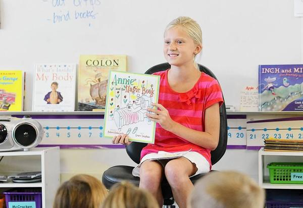 "Grace Vaughan, 10, a fourth-grade student at Mariners Elementary School, reads her first published book, ""Annie and the Magic Book,"" to a group of kindergartners at the school on Wednesday."