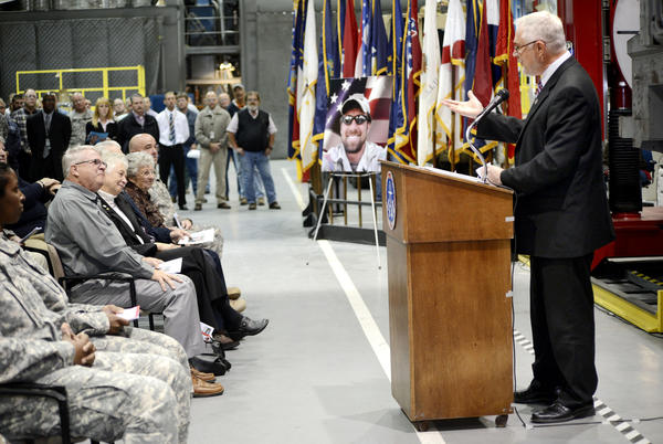 Franklin County Commissioner Bob Thomas speaks at a ceremony Wednesday dedicating the depot's new route clearance vehicle positioner to the memory of U.S. Army Master Sgt. Benjamin F. Bitner, who died in Afghanistan and is seen in the poster at left.