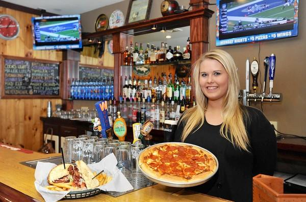 Jenna Smith, bartender at the Pickled Egg Pub in Wilson, holds a mixed pizza made with garlic and tomato sauce topped with pepperoni.