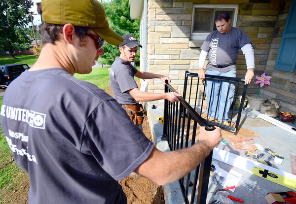 Triad Engineering Inc employees Billie Swailes, Bradley Reynolds and Jonathan Taylor, install a porch railing on Paulette Wright's Maugansville home Wednesday during the United Way of Washington County Day of Caring.