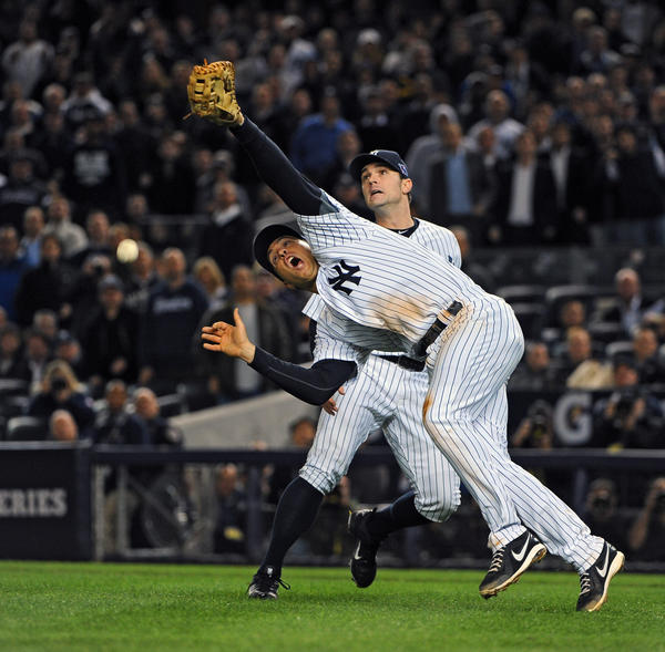 Yankees' Mark Teixeira dropped an infield fly by Oriioles' Mark Reynolds after running into his own pitcher David Robertson, right, in the top of the12th  inning. The Yankees defeated the Orioles by score of 3 to 2 in 12 innings to win game three of the ALDS at Yankees Stadium.