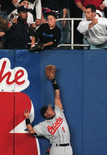 Yankees fan Jeffrey Maier, top, reaches over the right-field fence at Yankee Stadium to knock Yankees shortstop Derek Jeter's home run into the stands above Orioles right fielder Tony Tarasco in the bottom of the eighth inning in Game 1 of the American League Championship Series on Oct. 9, 1996. The home run tied the game, 4-4, and the Yankees won in the bottom of the 11th when center fielder Bernie Williams hit a solo home run off Orioles relief pitcher Randy Myers.