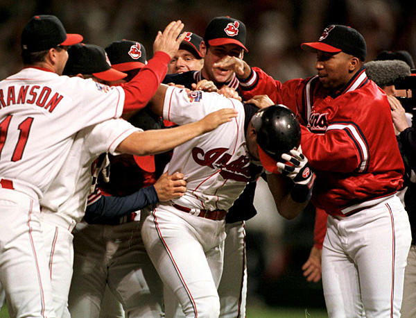 Cleveland Indians catcher Sandy Alomar Jr., center, is mobbed by his teammates after driving in the winning run in the bottom of the ninth inning in Game 4 of the American League Championship Series on Oct. 12, 1997. Alomar singled to knock in the Indians' Manny Ramirez for an 8-7 victory after the Orioles tied the game in the top of the ninth.