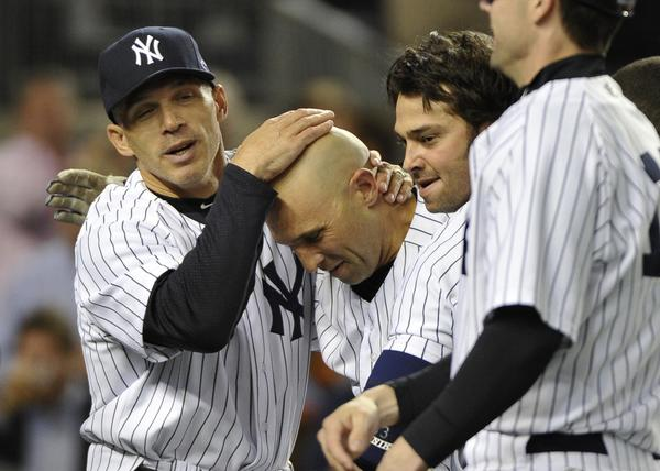 New York Yankees manager Joe Girardi (L) and Nick Swisher congratulate Raul Ibanez after he hit the game winning walk off solo home run against the Baltimore Orioles.