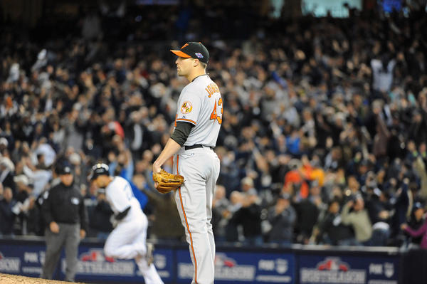 A dejected Orioles closer Jim Johnson, right, watched as Yankees' Raul Ibanez, left, rounded the bases after his game-tying homerun in the ninth inning. Ibanez also hitted the game-winning homerun in the 12th inning. The Yankees defeated the Orioles by score of 3 to 2 in 12 innings to win game three of the ALDS at Yankees Stadium.