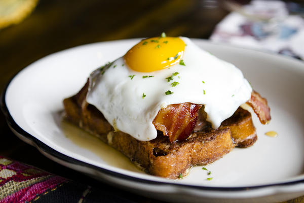 Grange Hall Burger Bar's open-faced breakfast burger consists of cinnamon French toast, a grass-fed beef patty, Canadian bacon, applewood-smoked bacon, cheddar, maple syrup and a fried egg.