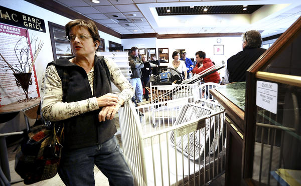 Judy Hoffman waits in line to pay for her finds, a crib and a pair of fans, on Thursday morning at the liquidation sale held at the former Hagerstown Hotel & Convention Center.