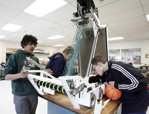 Saikiran Ramanan, 15, Corey Hoard, 17, and Guy Burstein, 16, of Circuit Breakers 696, after 15 straight hours, continue work on their robot at Clark Magnet High School in La Crescenta. The school received a 920 API score.