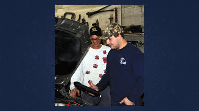 Mechanics Dan Brown and Ian Will test the battery on an old Volkswagen in their shop at Berlin Auto.