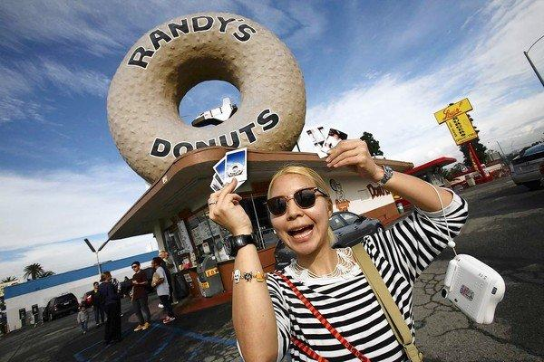 Tourist Mika Shima, 26, of Tokyo holds up photos she took of Randy's Donuts.