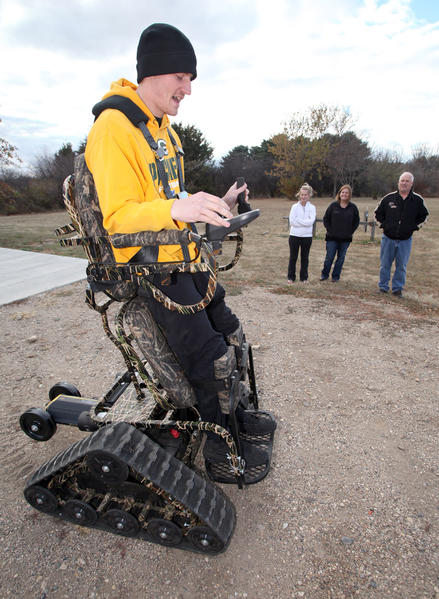 Cole Truebenbach operates the Action Trackstander that allows him to stand and move around outdoors as his girlfriend and parents look on.