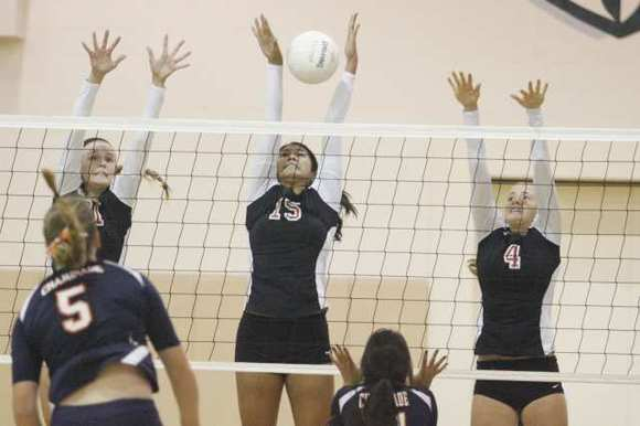 FSHA's Katie Conley, from left, Megan Bacall and Maddie Peterson block a spike against Chaminade.