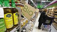 A customers buys organic products in the Bio foods section at Carrefour Planet supermarket in Nice Lingostiere