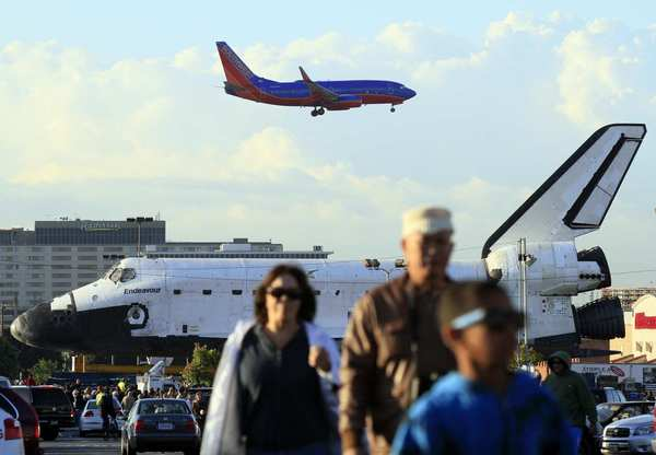 A Southwest Airlines flight comes in for a landing as the space shuttle Endeavour is parked to reconfigure the transporter that is carrying the shuttle on the two-day trek to the California Science Center.