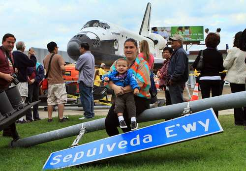 Tanya Isaacson, 37, and her one year old son Cameron Jimenez sit on a traffic signal to get their picture taken in front of space shuttle in Westchester.