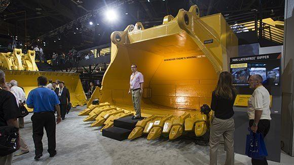 Dmitry Golitsyn of Moscow stands in a new latchfree dipper at the Caterpillar booth during the MINExpo International 2012 in Las Vegas.