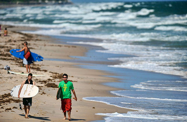 Vladimir Zakrevski and David Mills (l-r) leave the beach in Manalapan after a day of surfing Friday's big seas.  North northeast winds gusting to 25 knots built the seas to five to seven feet with occasional nine footers according to the National Weather Service marine forecast.  Conditions are expected to remain rough through Sunday night.