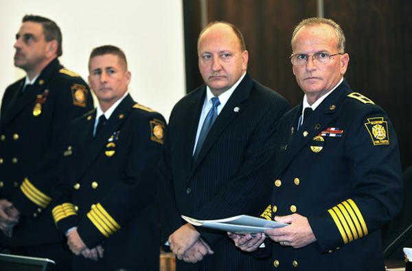 Fire Chief Robert Scheirer, right, and Mayor Ed Pawlowski, second from right, watch as firefighters receive awards. This was at the 2012 Annual Allentown Firefighters Fire Prevention & Awards Ceremony held in Allentown City Council Chambers during Fire Prevention Month Friday.