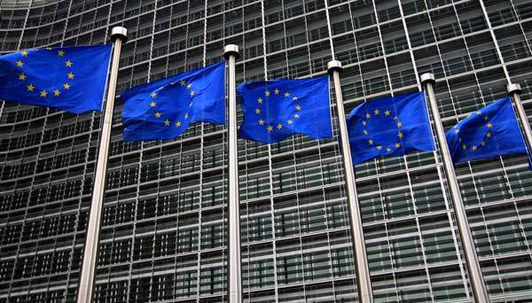 European Union flags fly in front of the European Commission headquarters in Brussels.