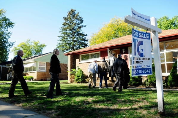 Participants enter a home on Hiawatha Drive in Elgin during a foreclosure bus tour.
