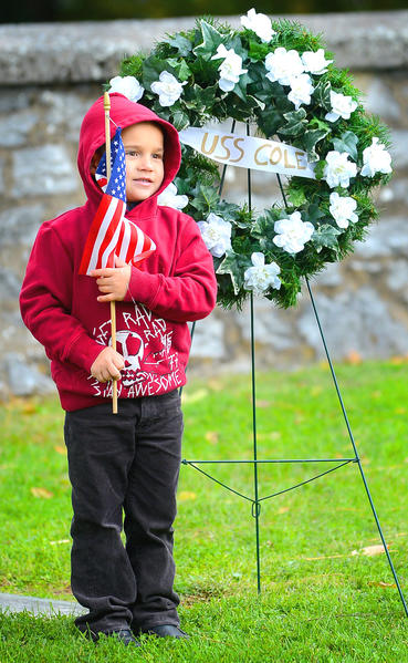 Cole Payne, 5, stands at the grave of his late uncle SN US Navy Craig Wibberley Friday at St Mark's before the start of a commemoration of the USS Cole bombing victims.