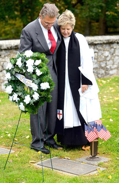 Tom Wibberley, left, father of the late SN Craig Wibberley USN, gets a comforting hug from the Rev. Anne Weatherholt at Craig's grave after a USS Cole Remembrance Day ceremony Friday at St Mark's Episcopal Church.