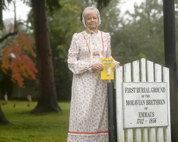 "Emmaus author MaryAnn Millerholds a copy of her new book in God's Acre cemetery in Emmaus. The cemetery is one of the subjects for her book ""Legends, Myths and Ghost Tales from Emmaus, PA."""