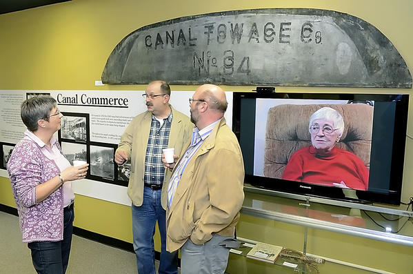 Hagerstown resident Dan McQuaid, middle, explains the C&O Canal to Wesel, Germany residents Monica and Alois Van Husen during their visit to Discovery Station Friday evvening.