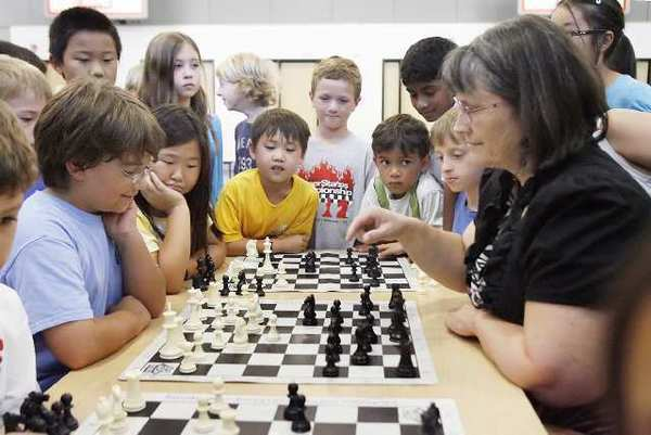 Max Totten, 11, sits across from chess master Ruth Haring with students from the Palm Crest Chess Club quietly watching at Palm Crest Elementary.
