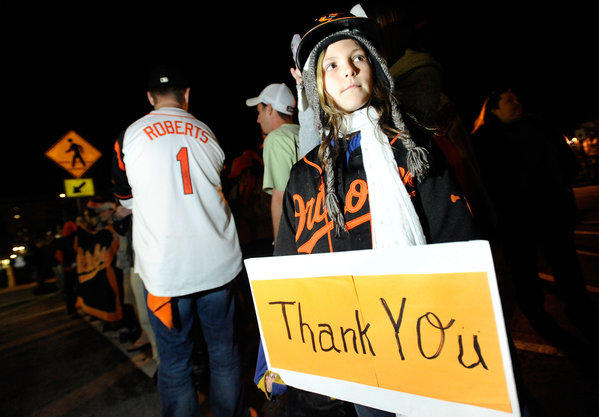 Baltimore Orioles fan Alicia Friskey, 10, of Rosedale, waits for the team to arrive at Oriole Park at Camden Yards in Baltimore late Friday, Oct. 12, 2012 after losing the deciding Game 5 of an American League Division Series against the New York Yankees.