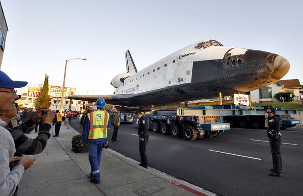The Space Shuttle Endeavour began its second day of its last trek to the California Science Center on Manchester Blvd. in Inglewood on Saturday, Oct. 13, 2012.  Thousands cheered and the 2001: A Space Odyssey theme song played on loud speakers as Endeavour arrived at the Forum.  (Raul Roa/Staff Photographer)