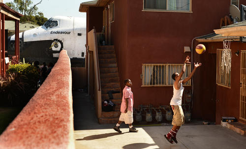 Traymond Harris, left, and Ryan Hudge play basketball as the space shuttle Endeavour passes by on Crenshaw Avenue in Inglewood.
