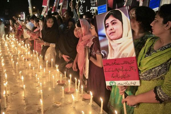 A Pakistani woman attending a vigil in Lahore holds a poster of Malala.