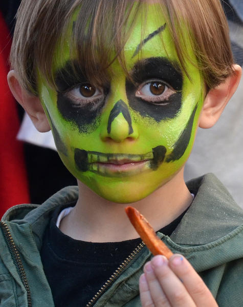 Painted as a neon skull Kelton Giamoni, 4, of Wind Gap enjoys fresh french fries during the 7th annual Harvest Festival in downtown Bethlehem on Saturday. The festival features beer and soup sampling, music, and activities such as a petting zoo and paint your own pumpkin./