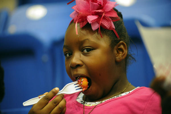 Samantha Salazar, 7, of Fort Lauderdale tries a candy coated mini-donut at the Festival of Chocolate at the Nova Southeastern University Arena Saturday were temped by all types of chocolates including miniature cupcakes by  Royal Treatz.