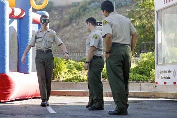 Los Angeles County Sheriff explorers Vicken Shahbazian, 15, from left, tries on DUI glasses as Sam Lopez, 19, and Richard Grandes, 19, watch Shahbazian walk in a straight line during an annual open house, which took place at Crescenta Valley's sheriff's station on Saturday.