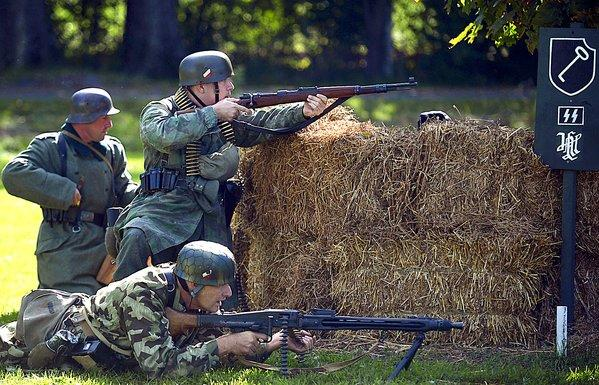 World War II reenactors portray German soldiers fighting against Allied forces during Williamsport's 5th Annual WWII Weekend at the Springfield Farm Saturday.