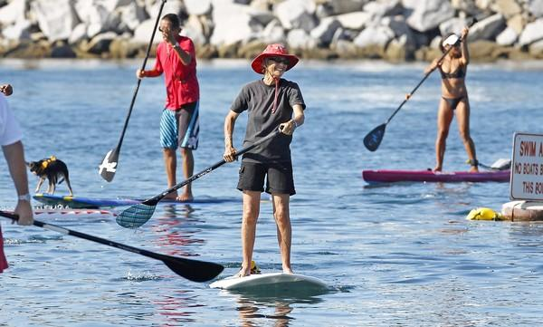 Newport Beach Mayor Nancy Gardner paddles into China Cove followed by members of the ABC Surf School on Saturday during the Paddle with the Mayor event in Newport Harbor.