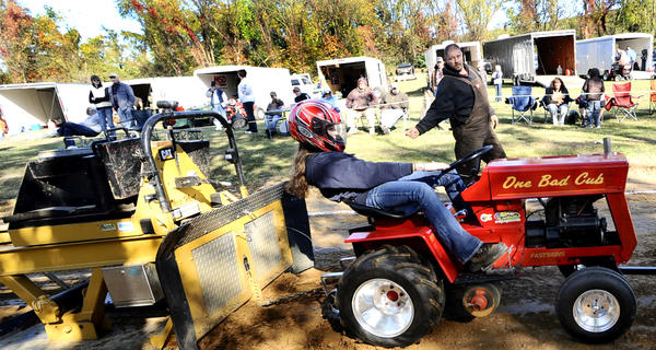 Norman Potter, rear, shows Brielle Winders, 13, how to lean to grab some traction and help steer her tractor during her 1st time pulling in the Youth Division of Pull For A Cure tractor pull held on Saturday in Smithsburg.
