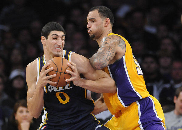 Lakers rookie center Robert Sacre tries to hold his position as Jazz center Enes Kanter works in the post during a preseason game Saturday night.