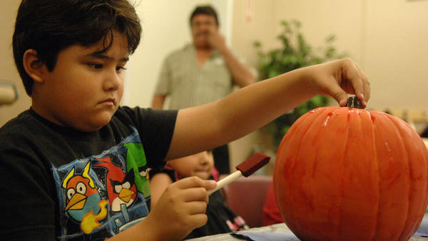 Noe Herrera, 8, paints his pumpkin at Michaels Arts and Crafts during a pumpkin decorating class for autistic children in El Centro on Saturday morning.
