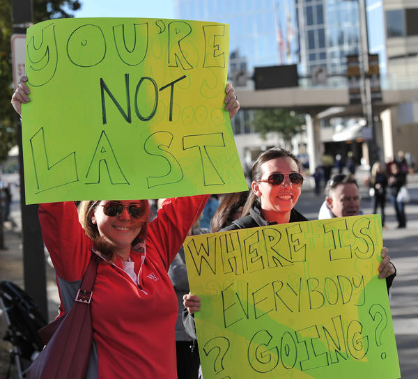 Left to right, Jill Grant and Lindsay Green, of Norwalk, Conn., hold up humorous signs as runners near the 9-mile marker on Light Street. They are waiting for Mike Grant, Jill's husband and Lindsay's brother who is running the marathon.