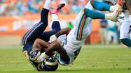 Lance Kendricks #88 of the St. Louis Rams is tackled by (R) Kevin Burnett #56 of the Miami Dolphins