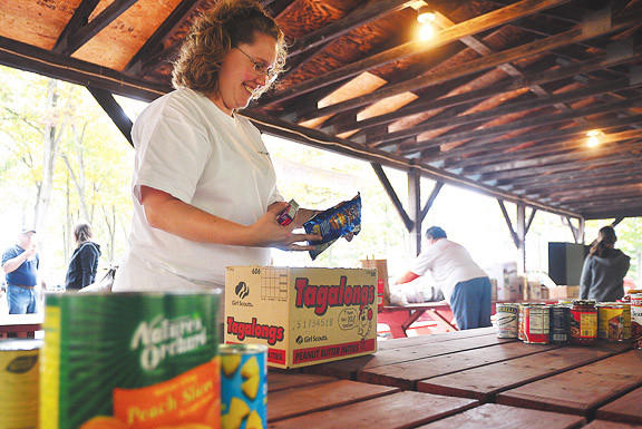 Heather Martin of Five Forks Food Pantry in Waynesboro, Pa., sorts through donated food items Sunday during the Fill the Food Banks Concert at Red Run Park in Rouzerville, Pa.