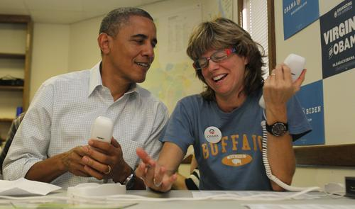 President Barack Obama shares a laugh with Suzanne Stern while making calls to volunteers during a stop at a local campaign office in Williamsburg on Sunday.
