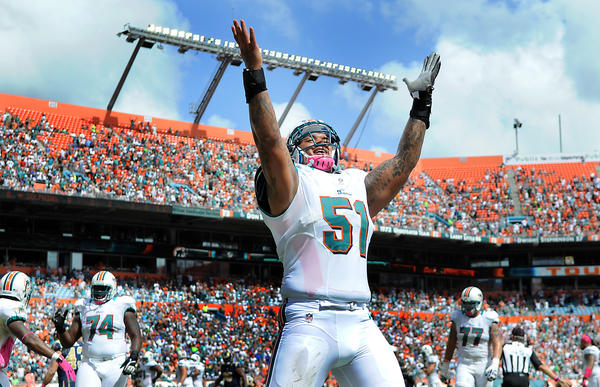 Dolphin's center Mike Pouncey celebrates the first quarter touchdown by reciever Marlon Moore.